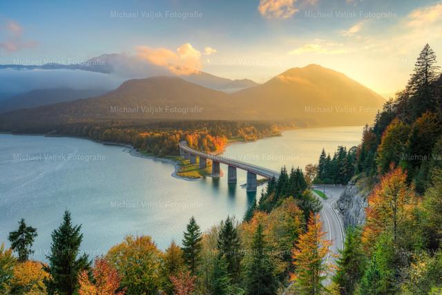 Herbst am Sylvensteinsee in Bayern | Genau rechtzeitig zum nahenden Sonnenuntergang tauchten die Sonnenstrahlen den Dunst und die Landschaft in ein goldenes Licht. Zusammen mit der Herbstfärbung der Blätter entstand dieses bunte Bild am Sylvensteinspeicher in Bayern.