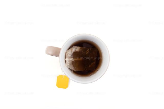 Teetasse | Von oben aufgenommene Teetasse mit Teebeutel über weißem Hintergrund.