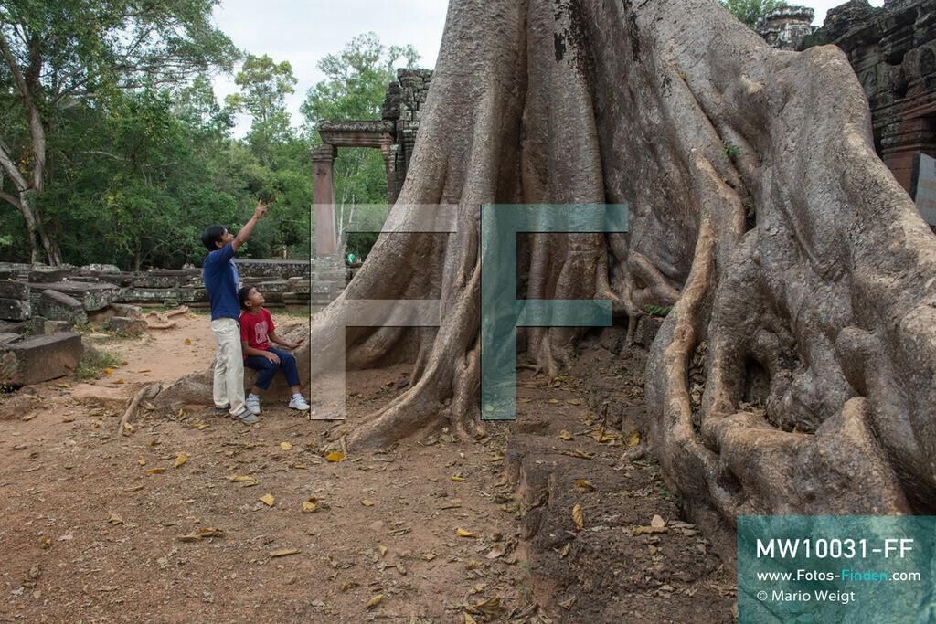 MW10031-FF | Kambodscha | Siem Reap | Reportage: Sombath erkundet Angkor | Sombath mit seinem Onkel Kim Sour an den großen Brettwurzeln eines Kapokbaumes im Tempel Banteay Kdei.  Der achtjährige Sombath lebt in Kambodscha im Dorf Anjan, sechs Kilometer westlich von Siem Reap entfernt. In seiner Freizeit nimmt ihn manchmal sein Onkel in die berühmte Tempelanlage von Angkor mit. Besonders mag er die riesigen Wurzeln der Kapokbäume, die auf den alten Mauern wachsen. Seine Lieblingstempel in Angkor sind Ta Prohm, Banteay Kdei und Preah Khan.  ** Feindaten bitte anfragen bei Mario Weigt Photography, info@asia-stories.com **