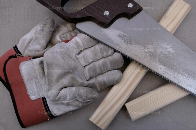 Fuchsschwanz mit Arbeitshandschuhen | Werkzeug-Stillleben mit Säge mit Arbeitshandschuhen und Holzstücken
