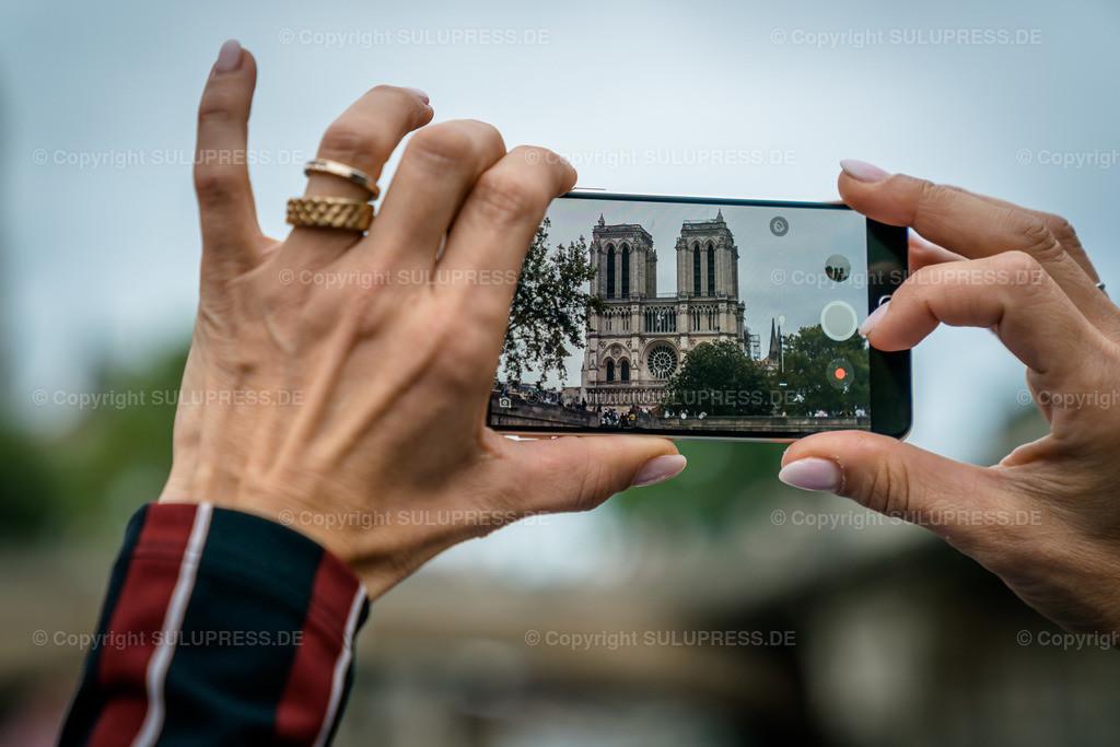 Handyfoto von Notre-Dame de Paris | 22.09.2019, die römisch-katholische Kirche Notre-Dame de Paris (Unsere Liebe Frau von Paris) ist die Kathedrale des Erzbistums Paris. Die Kirche ist der Gottesmutter Maria geweiht und wurde in den Jahren von 1163 bis 1345 gebaut. Somit ist es eines der frühesten gotischen Kirchengebäude Frankreichs. Ihr Name lautet auf Französisch Cathédrale Notre-Dame de Paris, oft einfach nur Notre-Dame. Ihre charakteristische Silhouette erhebt sich im historischen Zentrum von Paris auf der Ostspitze der Seine-Insel Île de la Cité im 4. Pariser Arrondissement. Nach dem Großbrand am 15. April 2019 wird das Gottesthaus wieder aufgebaut und ist derzeit eine Großbaustelle. Dennoch war, ist und bleibt Notre Dame eines der beliebtesten Fotomotive und wird wie hier mit einem Smartphone oft fotografiert.