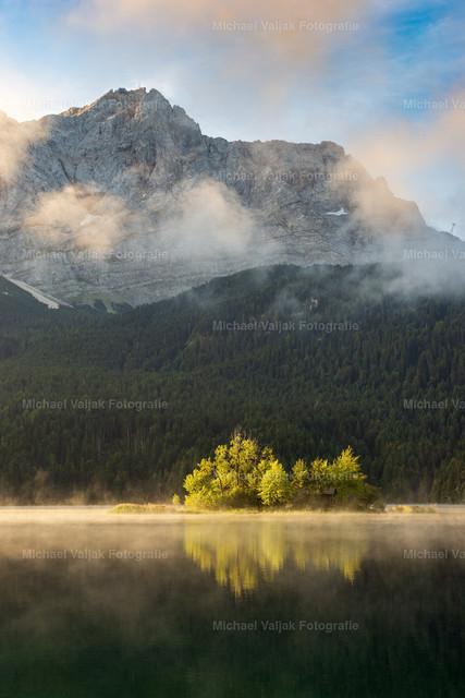 Morgens am Eibsee   Blick vom Ufer des Eibsees zur Maximiliansinsel und Zugspitze. Nebel wabert über den See, die ersten Sonnenstrahlen des Tages treffen auf die Insel und tauchen den Nebel in ein schönes warmes Licht.