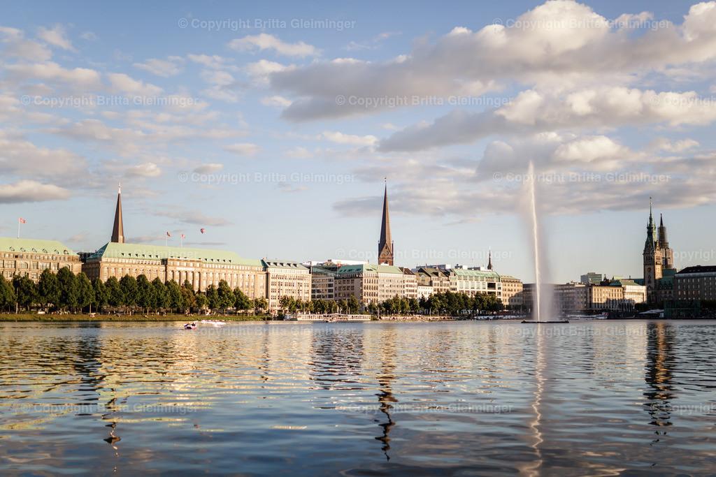 Hamburg - Binnenalster | Mitten in der Hamburger Innenstadt befindet sich ein großer See, zumindest hat es den Anschein, denn der See ist großes Becken in dem sich der Fluß Alster zur Binnenalster ausbreitet. In der Mitte ist eine Fontäne und es tummeln sich hunderte Wasservögel auf dem Wasser, nicht zuletzt die Alsterschwäne. Die Ansicht zeigt den Blick auf den Ballindamm. Das große Gebäude mit dem grünen Dach in der Mitte der Prachtstraße ist das Geschäftshaus der Hapag-Lloyd.