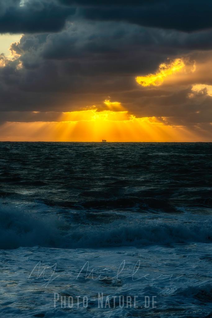 Die durchdringende Sonne | Die Sonne durchdringt mächtige Wolken vor einem aufziehendem Sturm an der italienischen Küste