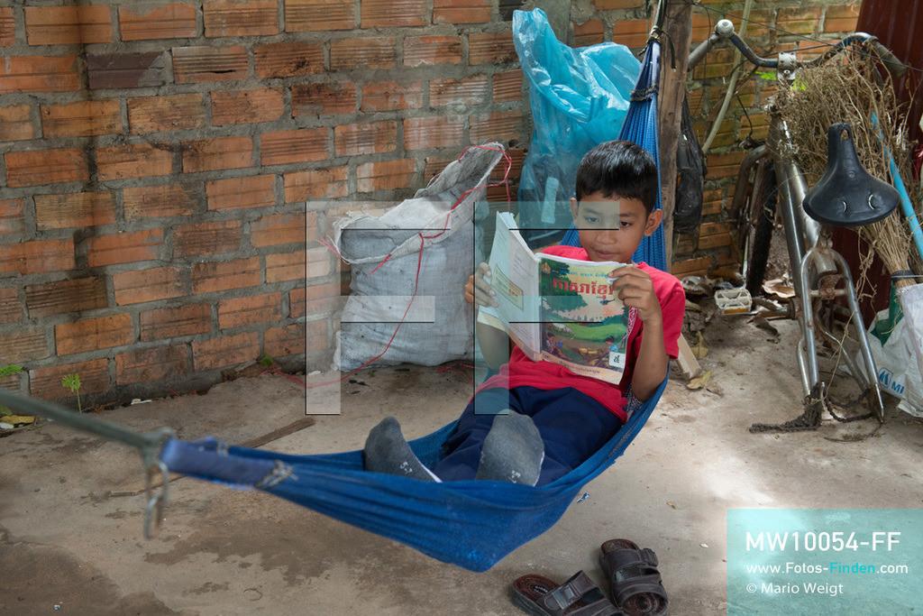 MW10054-FF | Kambodscha | Siem Reap | Reportage: Sombath erkundet Angkor | Zu Hause liest Sombath gern in der Hängematte. Der achtjährige Sombath lebt in Kambodscha im Dorf Anjan, sechs Kilometer westlich von Siem Reap entfernt. In seiner Freizeit nimmt ihn manchmal sein Onkel in die berühmte Tempelanlage von Angkor mit. Besonders mag er die riesigen Wurzeln der Kapokbäume, die auf den uralten Mauern wachsen. Seine Lieblingstempel in Angkor sind Ta Prohm, Banteay Kdei und Preah Khan.  ** Feindaten bitte anfragen bei Mario Weigt Photography, info@asia-stories.com **