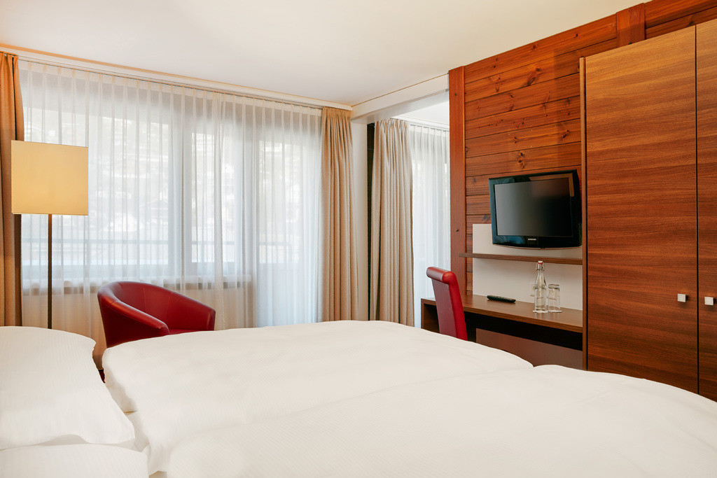 zimmer-superior-apartment-bett-fernseher-01-hplus-hotel-engelberg