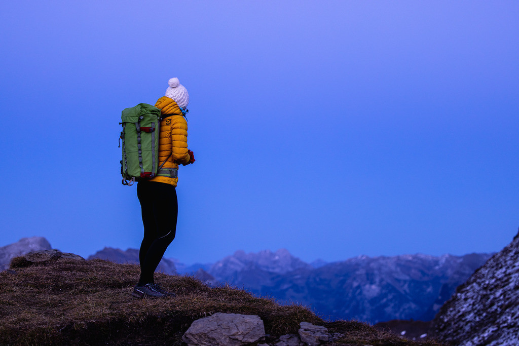 Woman in the mountains | A woman is standing on a hill in the mountains.