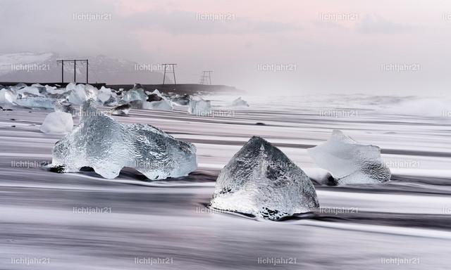 Morgenlicht am schwarzen Eisstrand | Eisblöcke liegen malerisch an einem schwarzen Vulkanstrand, die Bewegung der Wellen ist zu sehen (Langzeitbelichtung), darüber ein bewölkter Himmel mit roten Farbtönen des Sonnenaufgangs und Nebelschwaden - Location: Island, Jökulsarlon (Jökulsárlón)
