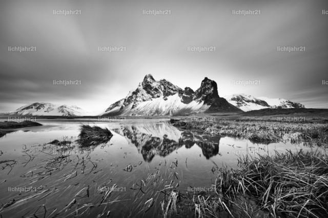Bergkette mit Spiegelung | Schneebedeckte Bergformation spiegelt sich in einem Teich, Grasbüschel im und neben dem Teich, Grashalme werden teilweise vom Wind bewegt, Wolkenbewegung wird durch Langzeitbelichtung sichtbar, große Tiefenwirkung, Schwarzweißbild - Location: Island, Südküste
