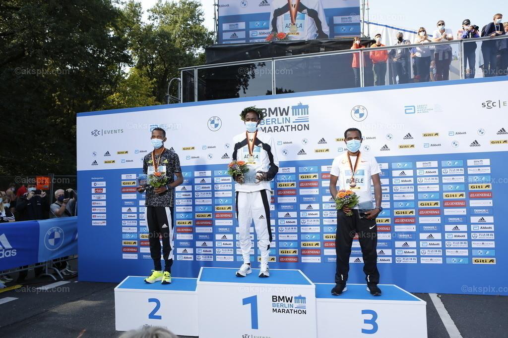 Guye Adola aus Äthiopien gewinnt den Berlin-Marathon 2021   26.09.2021, Berlin, Deutschland. Guye Adola aus Äthiopien gewinnt den 47. Berlin-Marathon in 2:05:45 Stunden. Den 2. Platz gewinnt der Kenianer Bethwel Yegon mit 2:06:14 Stunden und  den dritten Platz gewinnt der Top-Favorit Kenenisa Bekele mit 02:06:47 Strunden. Das Bild zeigt Bethwel Yegon, Guye Adola und Kenenisa Bekele.
