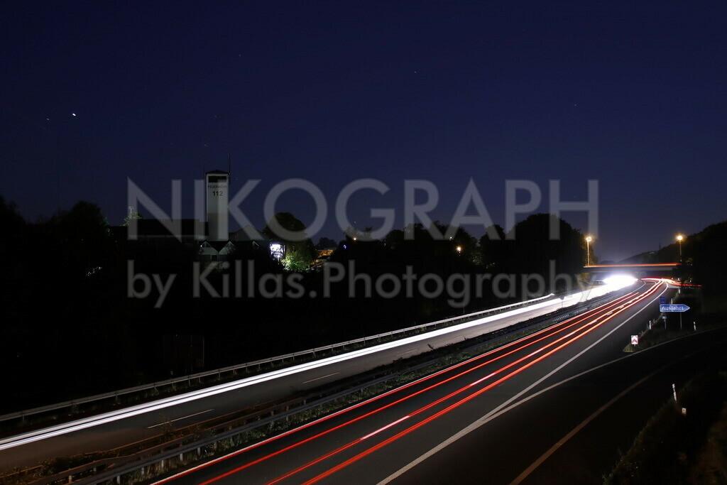 Die Autobahn A46 in Iserlohn | Nachtaufnahme an der Autobahn A46 an der Ausfahrt Iserlohn-Zentrum. Die Scheinwerfer der Autos ziehen Lichtspuren über die Autobahn.  Der Schlauchturm der Feuer- und Rettungswache der Berufsfeuerwehr Iserlohn ragt in den Sternenhimmel.