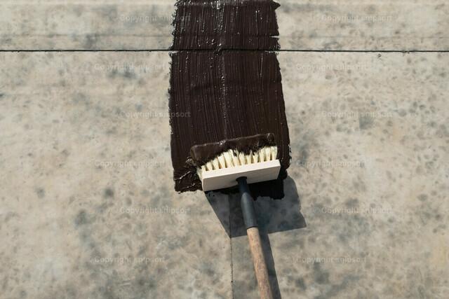 Sanieren eines Flachdachs mit Bitumenmasse und einem Quast