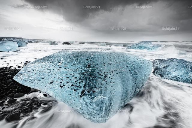 Großer Eisblock in der Brandung | Großer Eisblock in blauen Farbtönen an einem Strand mit starker Brandung, die Wasserbewegung ist zu sehen (Langzeitbelichtung, Bewegungsspuren), darüber ein kontrastreicher grau bewölkter Himmel - Location: Island, Jökulsarlon (Jökulsárlón)