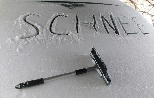 Auto vom Schnee freifegen | Konzept für ein zugeschneites Auto mit Schneefeger.