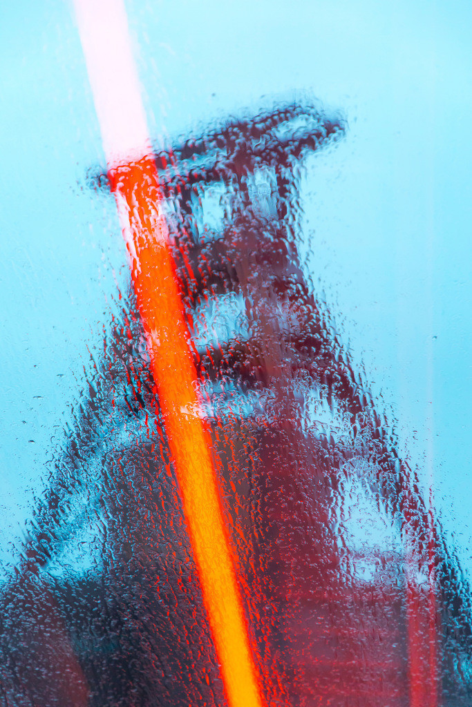 JT-180312-085 | Welterbe Zeche Zollverein, Fördergerüst Schacht 12, Essen, gesehen durch die Regennasse Glasscheibe der Rolltreppe zum Ruhrmuseum, Lichtreflexe der rot beleuchteten Fahrtreppe,