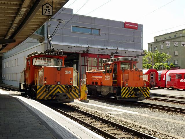 RhB Ge 3/3 214 & RhB Gm 2/2 233   Vor dem Depot in Chur stehen zwei Rangierlokomotiven. Im Hintergrund stehen Wagen vom Glacier-Express.