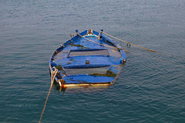 Halb versunkenes Fischerboot | Ein mit Wasser vollgelaufenes Ruderboot im Meer.