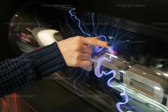 Plasmalampe | Eine Frau hält einen Finger an eine Plasmalampe.