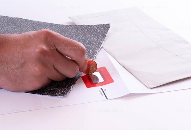 Freirubbeln von Geheimcode | Eine Hand rubbelt mit einer Münze den PIN Code frei