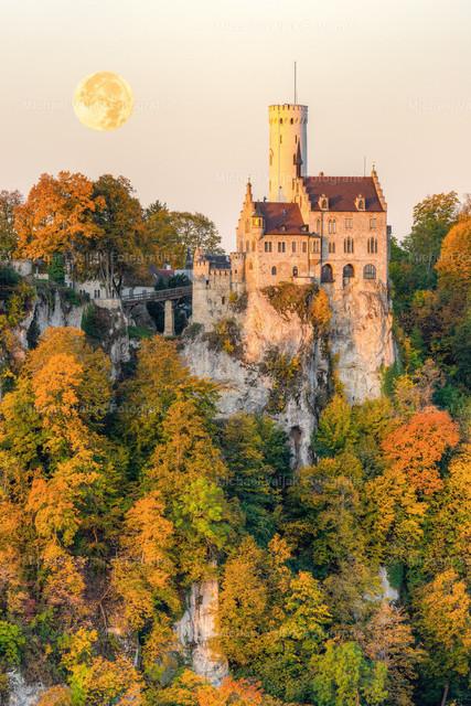 Schloss Lichtenstein im Herbst   Das Märchenschloss auf der Schwäbischen Alb, angeleuchtet von den ersten Sonnenstrahlen des Tages und mit untergehendem Mond.