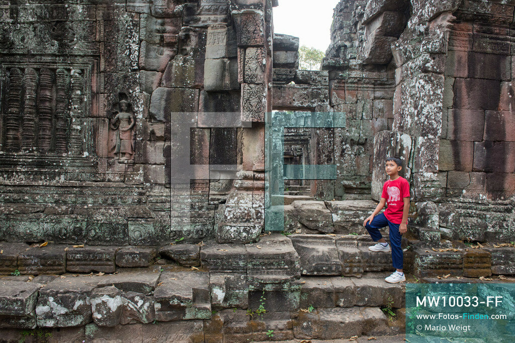 MW10033-FF | Kambodscha | Siem Reap | Reportage: Sombath erkundet Angkor | Sombath im Tempel Banteay Kdei.  Der achtjährige Sombath lebt in Kambodscha im Dorf Anjan, sechs Kilometer westlich von Siem Reap entfernt. In seiner Freizeit nimmt ihn manchmal sein Onkel in die berühmte Tempelanlage von Angkor mit. Besonders mag er die riesigen Wurzeln der Kapokbäume, die auf den alten Mauern wachsen. Seine Lieblingstempel in Angkor sind Ta Prohm, Banteay Kdei und Preah Khan.  ** Feindaten bitte anfragen bei Mario Weigt Photography, info@asia-stories.com **