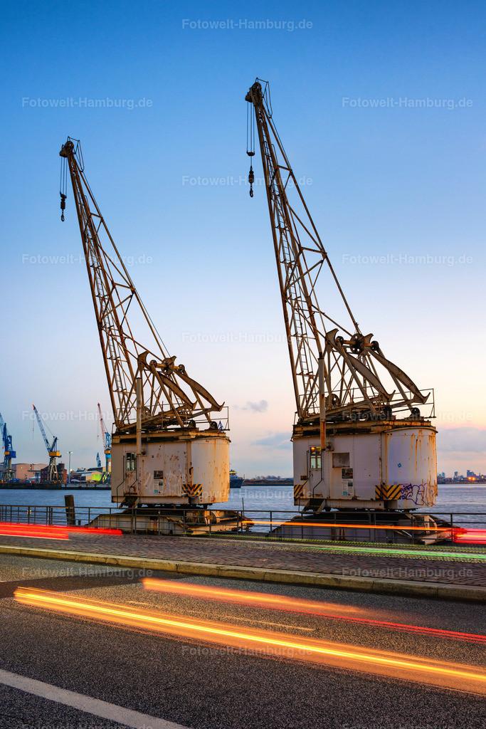 10200714 - Historische Hafenkräne am Abend | Historische Hafenkräne im Altonaer Holzhafen mit den Lichtern vorbeifahrender Autos.