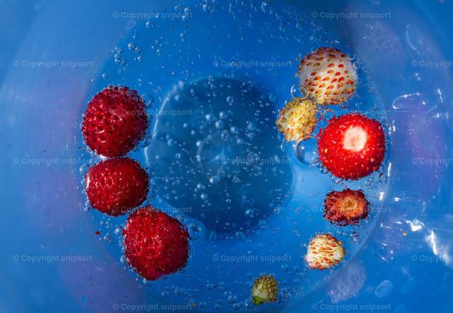 Mineralwasser mit Erdbeerstückchen | Sprudelndes Mineralwasser im blauen Becher mit kleinen Erdbeeren.