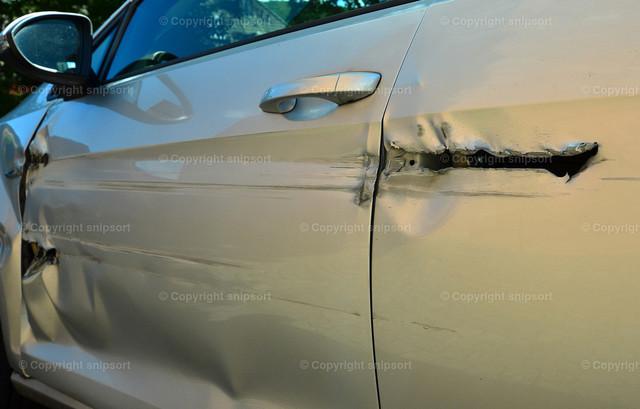 Auto mit Unfallschaden | Eine längs aufgerissene Karosserie eines Unfallfahrzeugs.