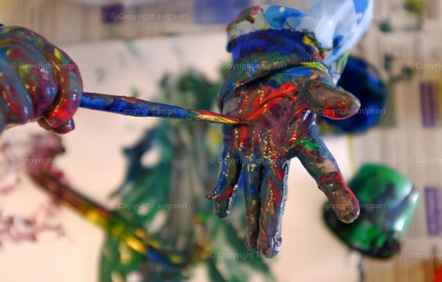Kleinkind beim Malen | Ein Kind bemalt seine Hand mit bunten Farben.
