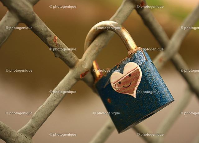 Liebesschloss blau mit Herz | blaues Vorhängeschloss mit weißem Herzen hängt an einem Gitter