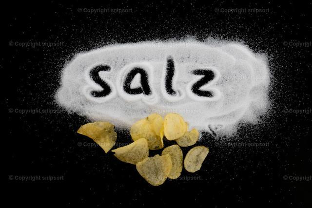 Konzept Salz mit Kartoffelchips | In einen auf dem schwarzen Hintergrund verstreuten Haufen handgeschriebenes Wort
