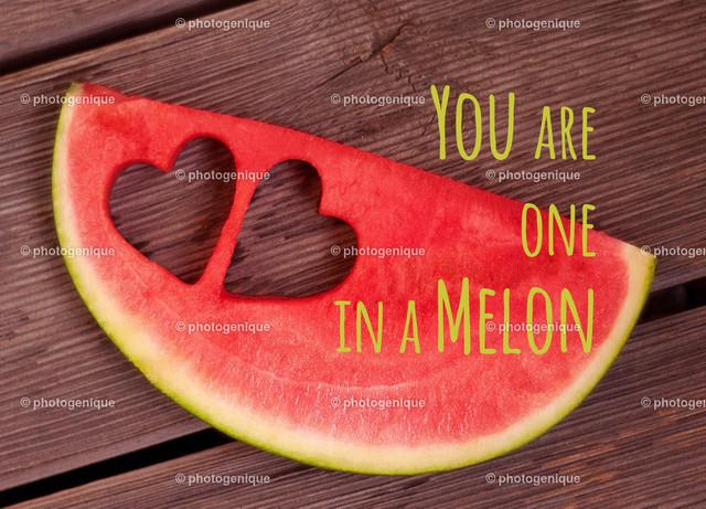 Postkarte You are one in a melon | Postkarte mit einer Scheibe einer roten Wassermelone mit zwei ausgestochenen Herzen und dem Text You are one in a melon