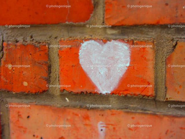 Grafitti Herz auf Mauer | weißes Grafitti Herz auf roter Ziegel-Mauer bei Tageslicht