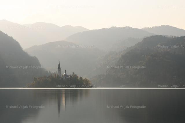 Bleder See in Slowenien | Die Insel Blejski Otok vor der Bergkulisse im Hintergrund an einem dunstigen Tag im Oktober.