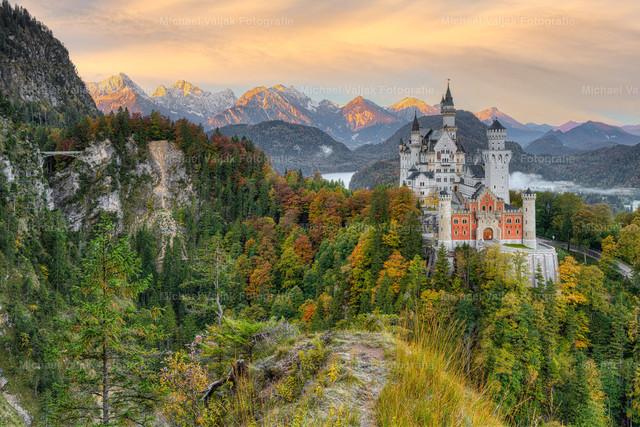 Schloss Neuschwanstein und Marienbrücke | Blick auf das Schloss Neuschwanstein und die Marienbrücke im Frühherbst, als die Bäume gerade anfangen, sich bunt zu färben. Zusammen mit einem prächtigen Sonnenaufgang ergibt sich dieses herrliche Farbenspiel an dem berühmten Märchenschloss im Allgäu in Bayern.