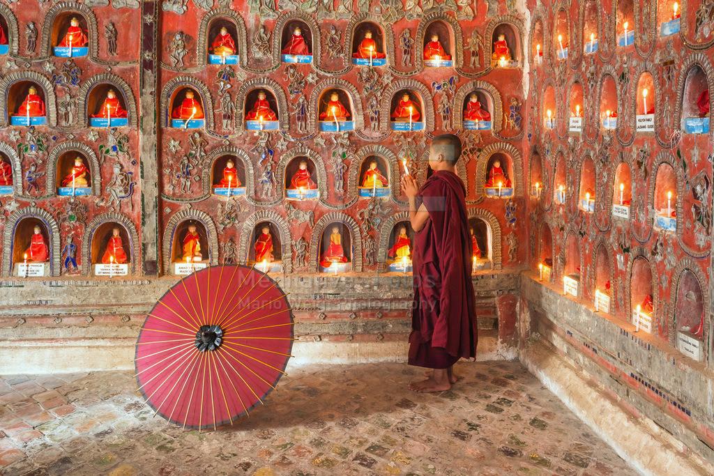 MW0115-5403 | Fotoserie DER ROTE SCHIRM | Betender Mönch vor Buddha-Statuen in einem buddhistischen Kloster am Inle-See