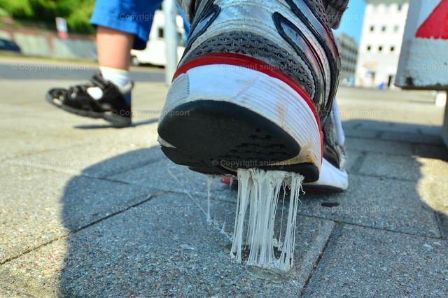 Klebender Kaugummi am Schuh | Ein Passant tritt auf einen klebrigen Kaugumi auf dem Bürgersteig