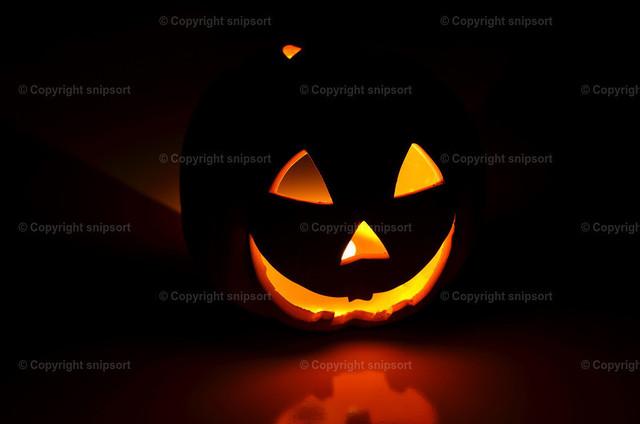 Halloween-Kürbis im Dunkeln | Silhouette von einem Halloweenkürbis mit glühenden Augen und Mund.