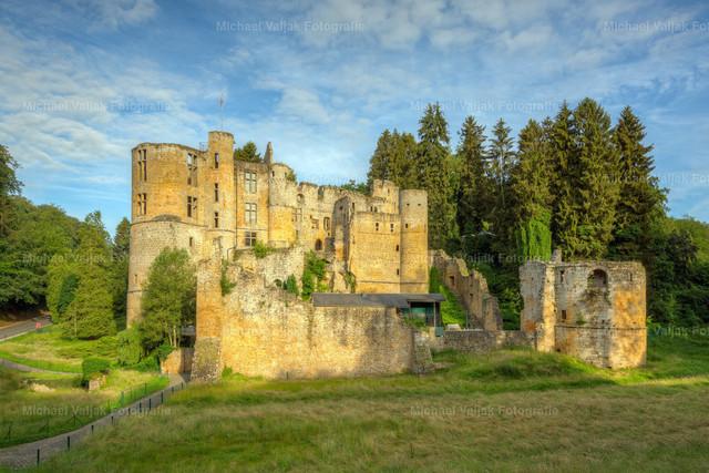 Burg Beaufort in Luxemburg | Die denkmalgeschütze Ruine der Burg Beaufort steht in der Gemeinde Befort in Luxemburg. Sie steht etwas südlich außerhalb des Ortskerns auf einem Felsvorsprung. Die Aufnahme zeigt die Burg im warmen Licht eines Sommermorgens.