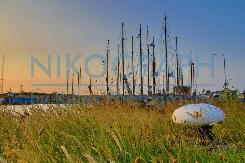 Hafenpoller im Gras | Ein Hafenpoller im Gras vor dem Abendhimmel über den Yachthafen von Oudeschild. Oudeschild liegt auf der niederländischen Nordseeinsel Texel. Mit über 1.200 Einwohnern ist Oudeschild der drittgrößte Ort der Insel. Im Oudeschild befindet sich auch der Fischereihafen von Texel sowie eine Marina mit rund 200 Liegeplätzen. Früher war in Oudeschild auch der Fährhafen. In den 1960er Jahren wurde in 't Horntje der neue Fährhafen gebaut. Durch die Lage an der Südspitze konnte die Passage zwischen Den Helder und Texel verkürzt werden.