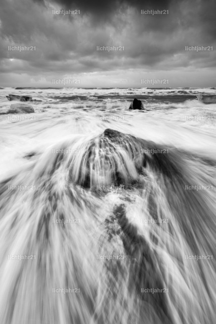 Eisblock mit Welle | Ein Eisblock wird an einem Strand schwarzen mit starker Brandung von einer Welle überspült, die Wasserbewegung ist zu sehen (Langzeitbelichtung, deutliche Bewegungsspuren), darüber ein kontrastreicher grau bewölkter Himmel, Schwarzweißbild - Location: Island, Jökulsarlon (Jökulsárlón)