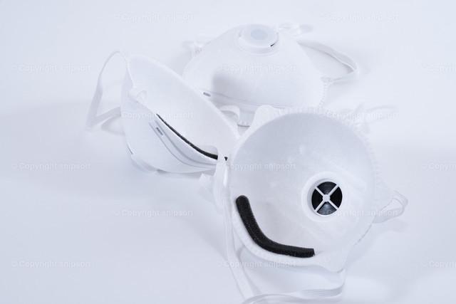 Atemschutzmasken auf schwarzem Hintergrund | Drei Feinstaub-Atemschutzmasken zum Schutz von Erregern über weißem Hintergrund