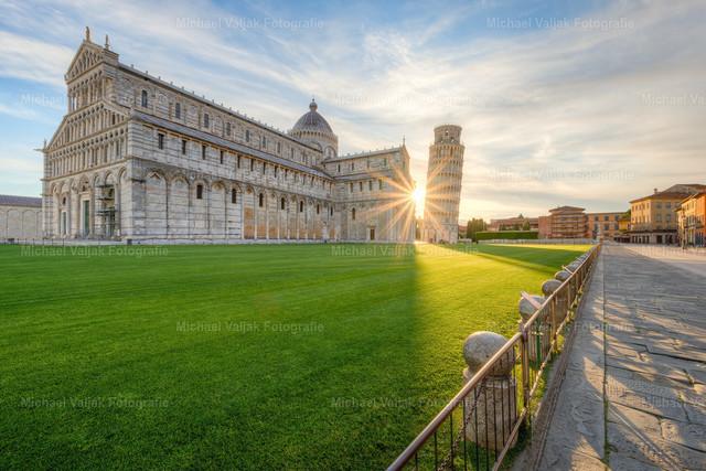 Ein Sonnenstern in Pisa  | Der Dom zu Pisa mit seinem schiefen Glockenturm kurz nach Sonnenaufgang.