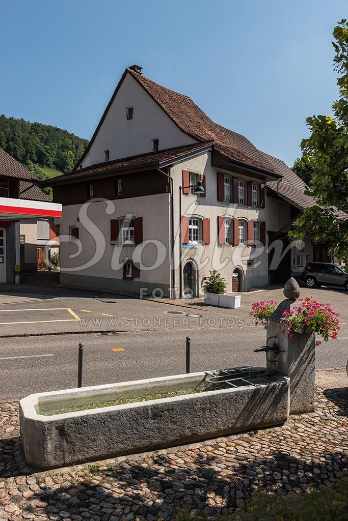 Dorfbrunnen, Ziefen (BL) | Dorfbrunnen (1821) bei der ehemaligen unteren Schmiede, im Hintergrund ein ehemaliges Rebbauernhaus (s'Peterhanse Huus), Ziefen im Kanton Baselland.