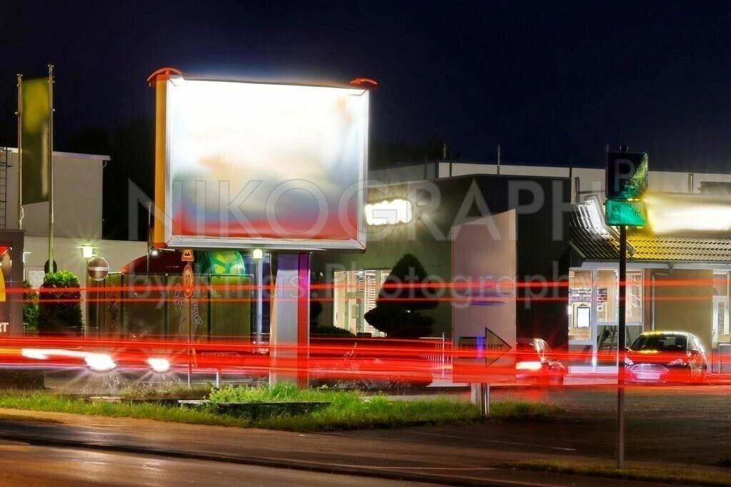 Außenwerbung bei Nacht | Eine City-Star-Werbeanlage an der Bundesstraße bei Nacht. Die vorbeifahrenden Fahrzeuge ziehen Lichtspuren durchs Bild und bringen Dynamik ins Bild.