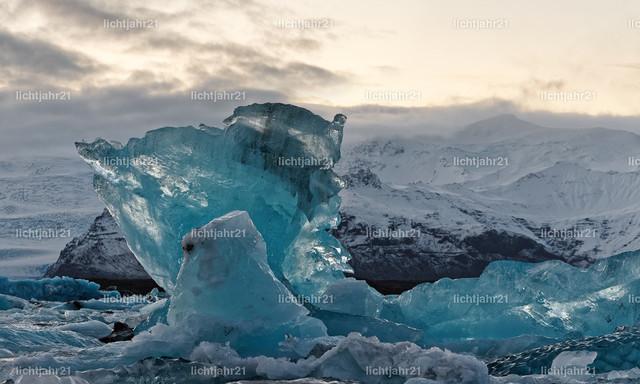 Abendlicht mit Eisformationen vor einem großen Gletscher | Gletscherlagune mit Eisformationen in verschiedenen Blautönen, Himmel mit gelbem Abendlicht, im Hintergrund als Kulisse ein gewaltiger Gletscher, Tiefenwirkung - Location: Island, Südküste, Gletscherlagune Jökulsarlon (Jökulsárlón)