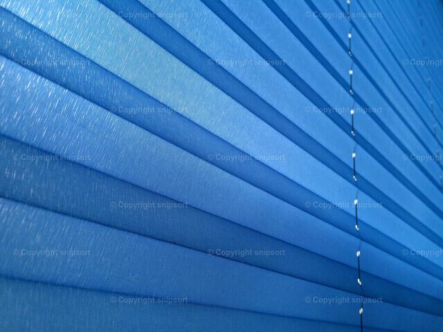 Blaues Plissee | Hintergrund mit einem blauen Plisseestoff mit diagonal zulaufenden Linien.