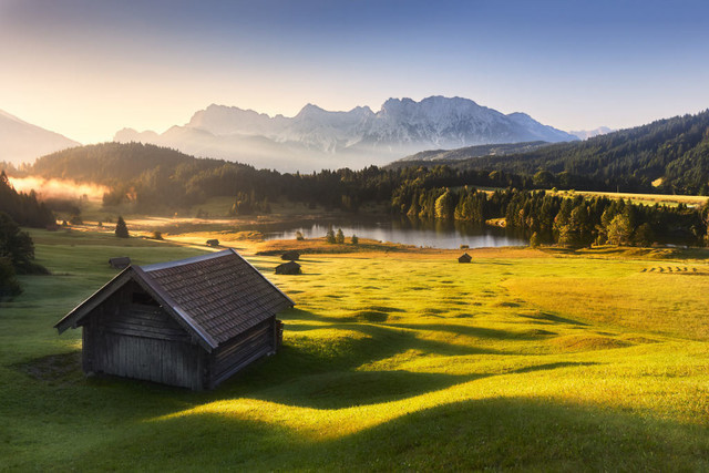 Traumhafte Berglandschaft am Geroldsee | Trotz der frühen Stunde kurz nach Sonnenaufgang löst sich der letzte Nebel bereits auf, bevor er über den Geroldsee kriechen kann. Das Licht streift über die sanften Buckelwiesen und die Heuschober sind Kulturzeugen in dieser fantastischen Berglandschaft.