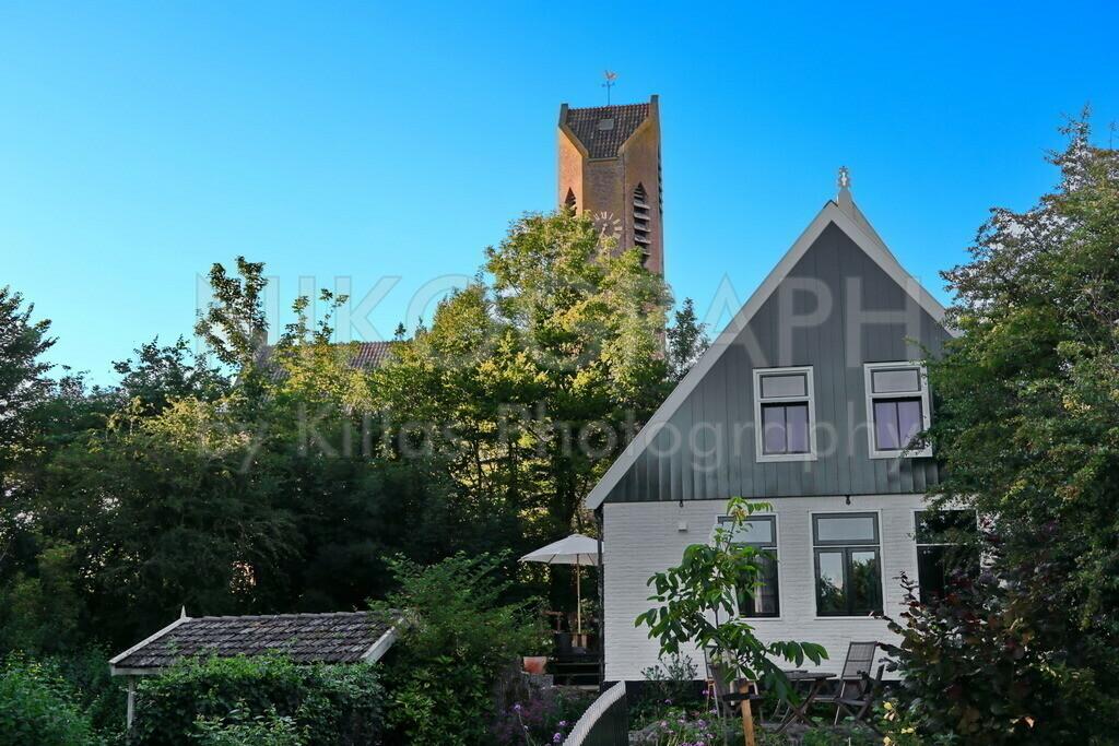 Kirchturm von De Waal auf Texel   Ein Haus im Dorf De Waal auf der Nordseeinsel Texel mit dem Kirchturm im Hintergrund. De Waal ist das kleinste Dorf der Insel Texel. De Waal besticht durch die Architektur der Häuser. Die gemütliche Atmosphäre in De Waal lädt zum Verweilen ein und bietet Entschleunigung pur.