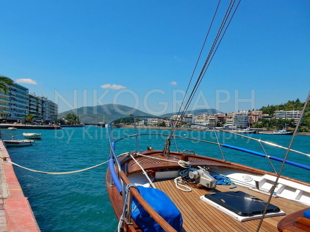 Waterfront of Chalkida | Ein Boot an der Strandpromenade von Chalkida auf der griechischen Insel Euböa. Im Hintergrund ist die alte Schwenkbrücke zu sehen, welche die Insel Euböa mit dem Festland verbindet.